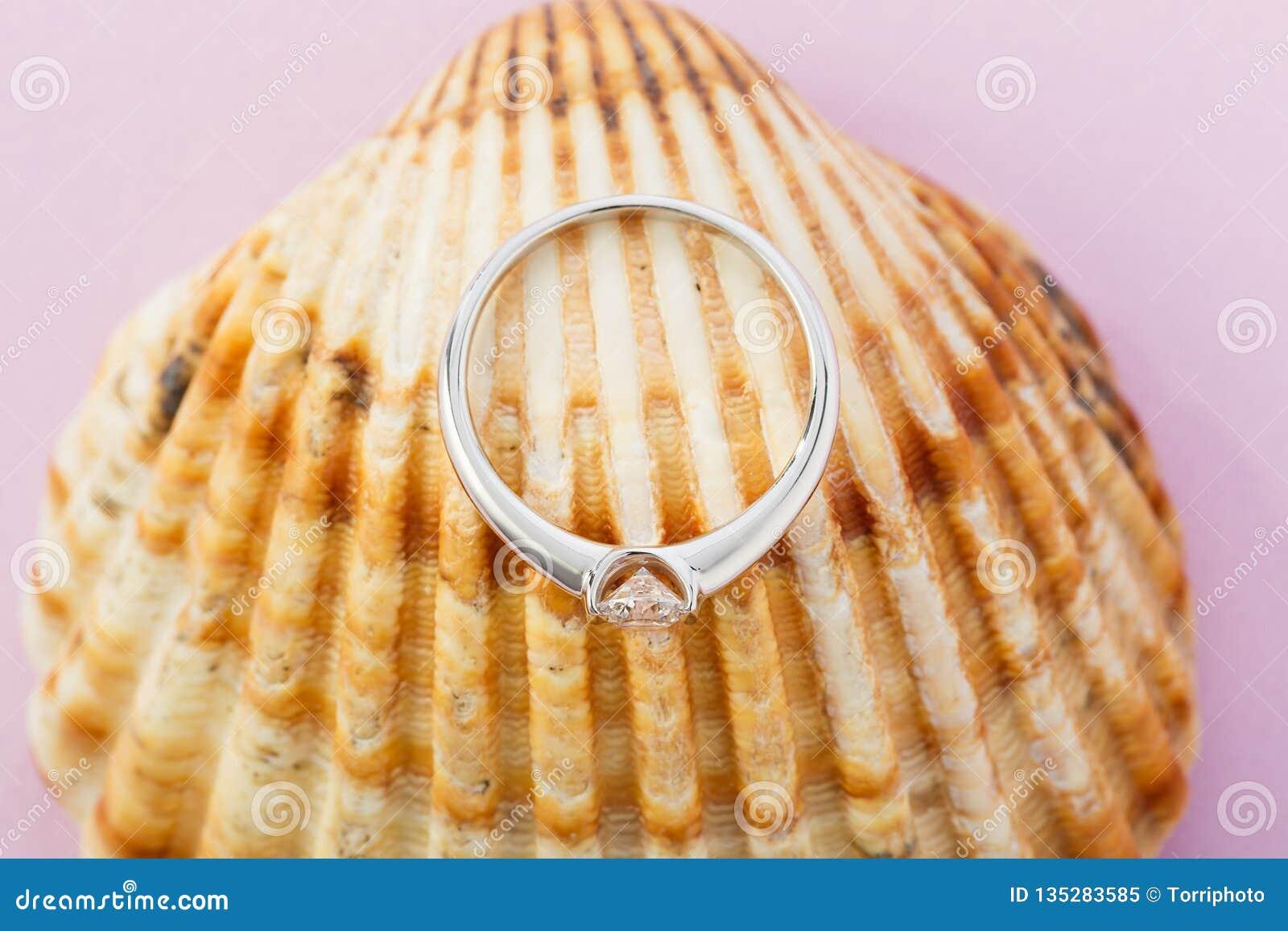 Anillo de compromiso del oro blanco con el diamante en fondo de la concha marina