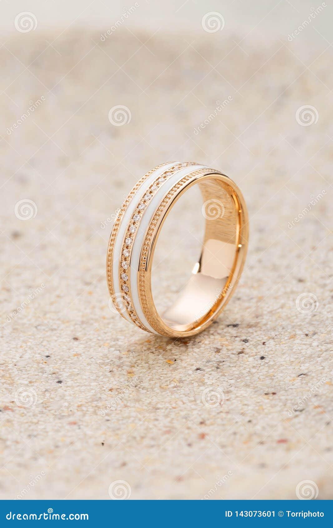 Anillo de oro con el esmalte blanco y diamantes en fondo beige de la arena