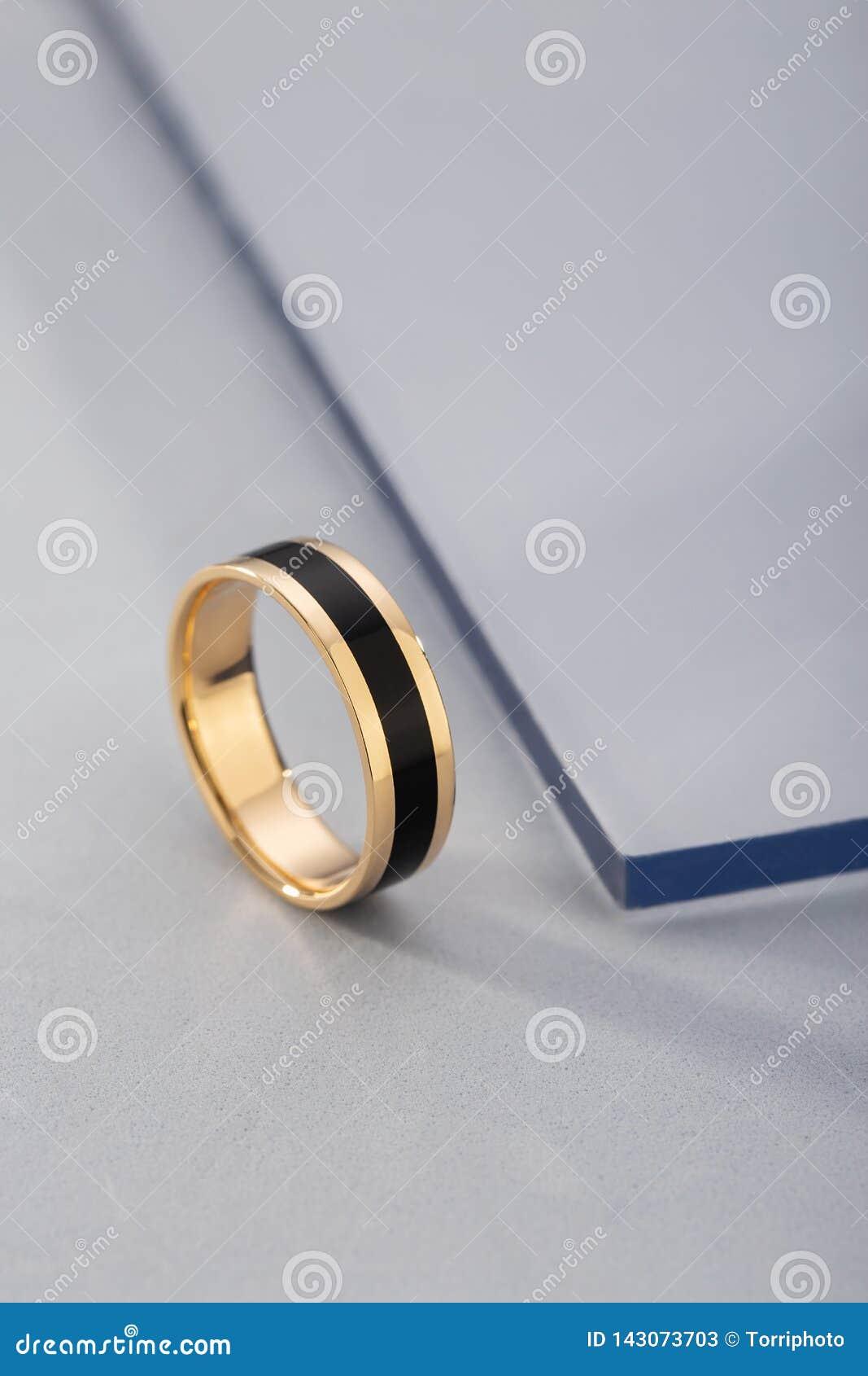 Anillo de oro con el esmalte negro en fondo azul