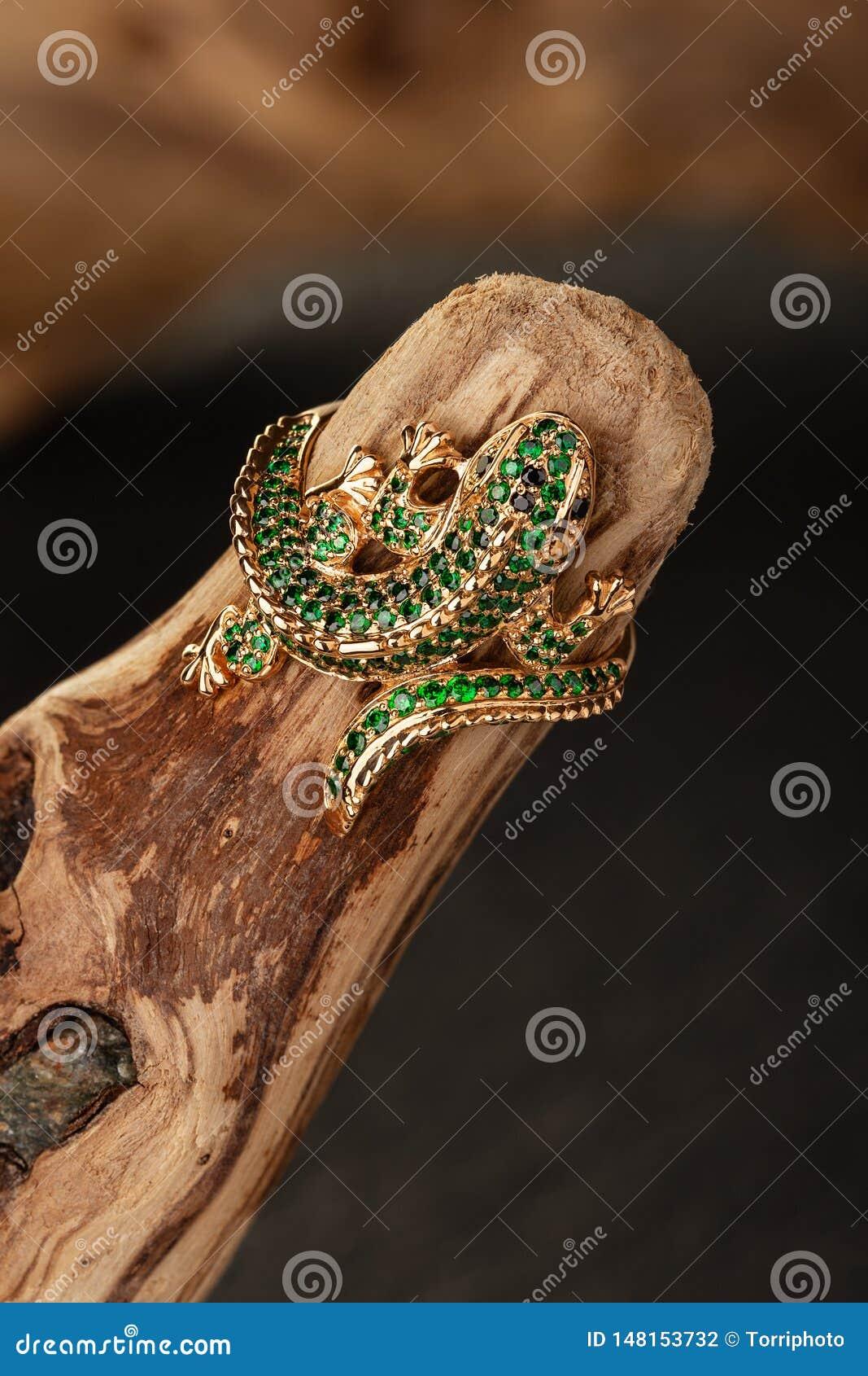 Anillo de oro de la joyería de la forma del lagarto con las piedras preciosas verdes en fondo de madera natural