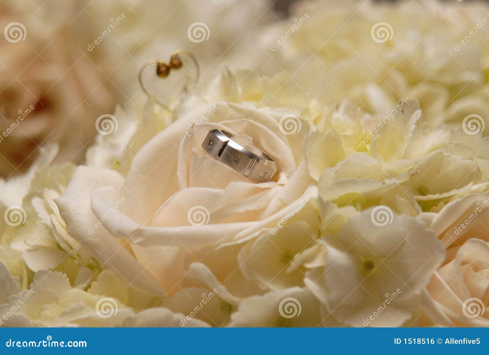 Anillo del novio en el ramo de la flor de la novia