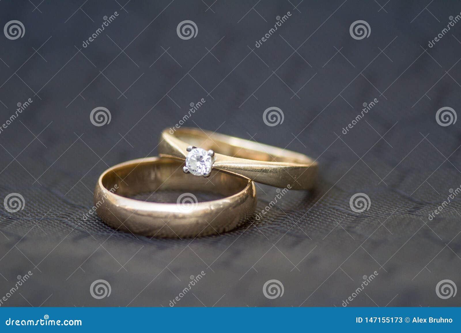 Anillos de bodas anillo con los breients Fondo gris Panal gris Macro dos anillos macros dos anillos macros