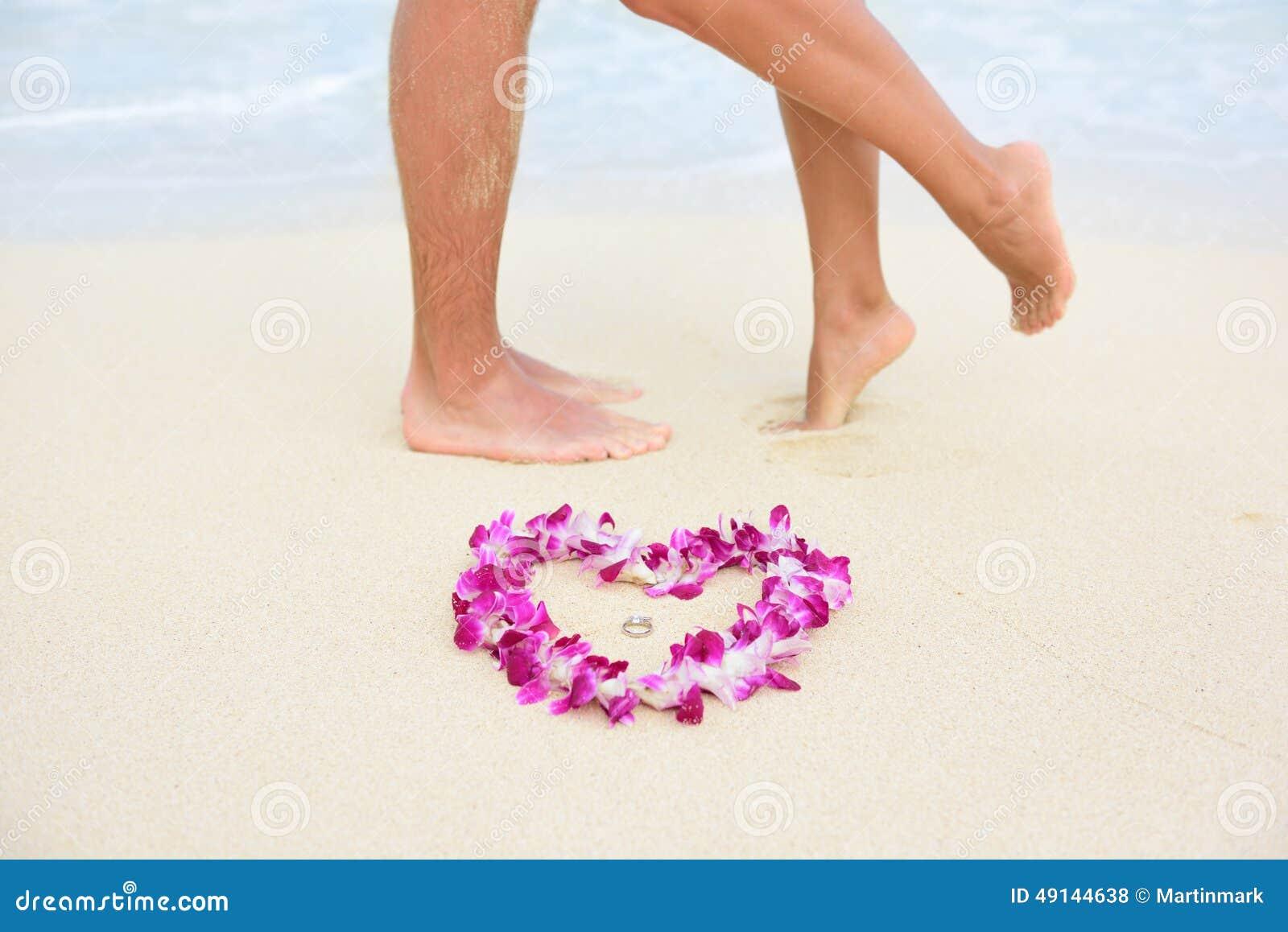 Anillos de bodas de playa con los pies de los pares que se besan