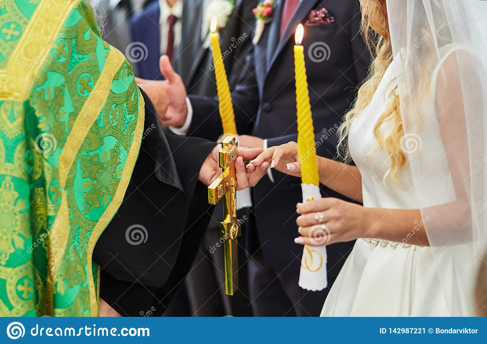 Anillos de bodas del intercambio de los recienes casados en una ceremonia en la iglesia