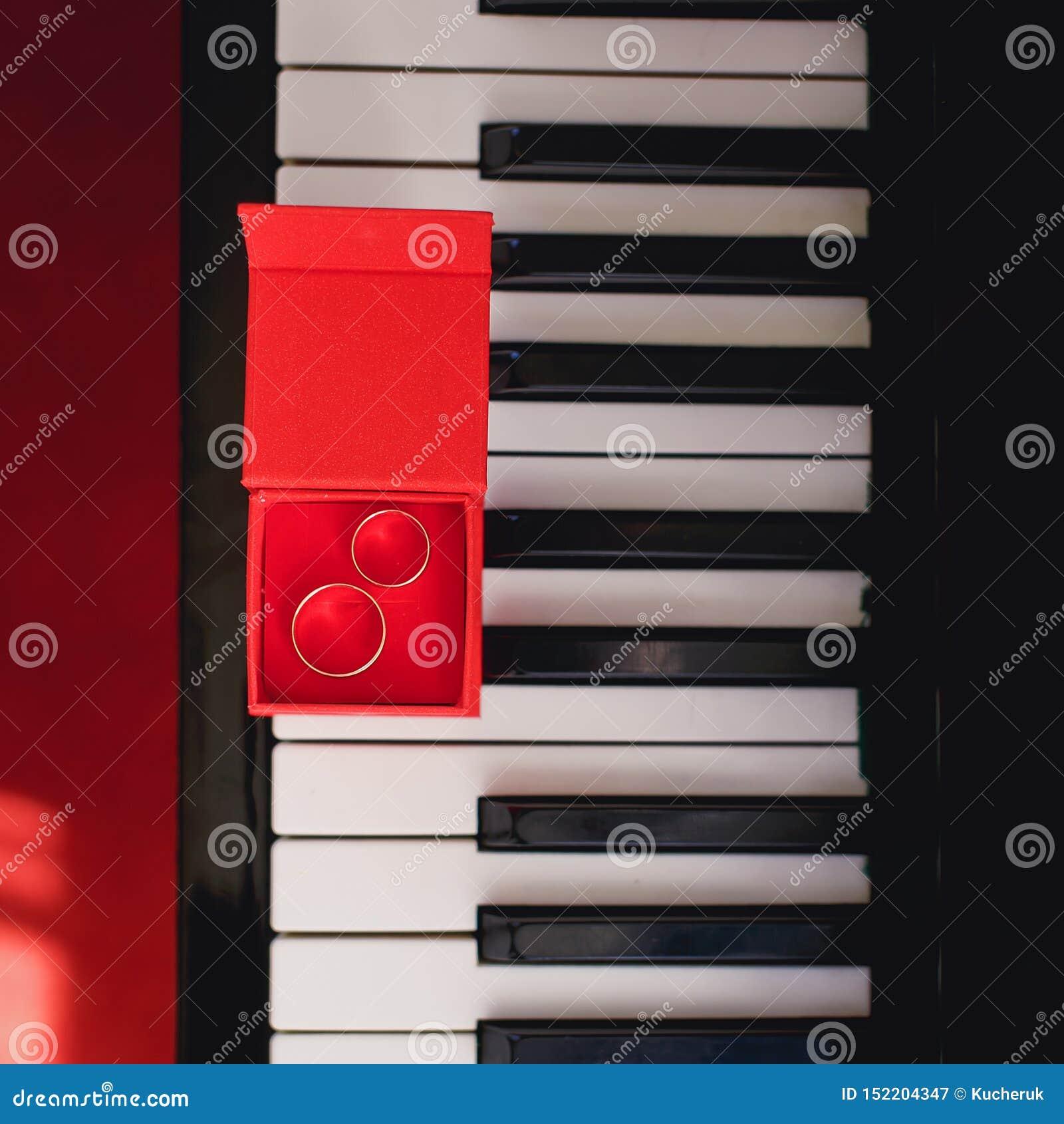 Anillos de bodas en caja roja en el piano