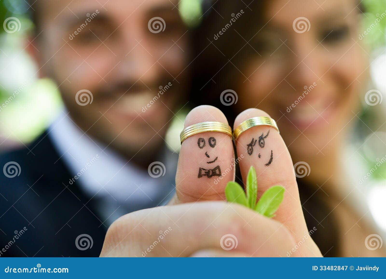 Anillos de bodas en sus fingeres pintados con la novia y el novio