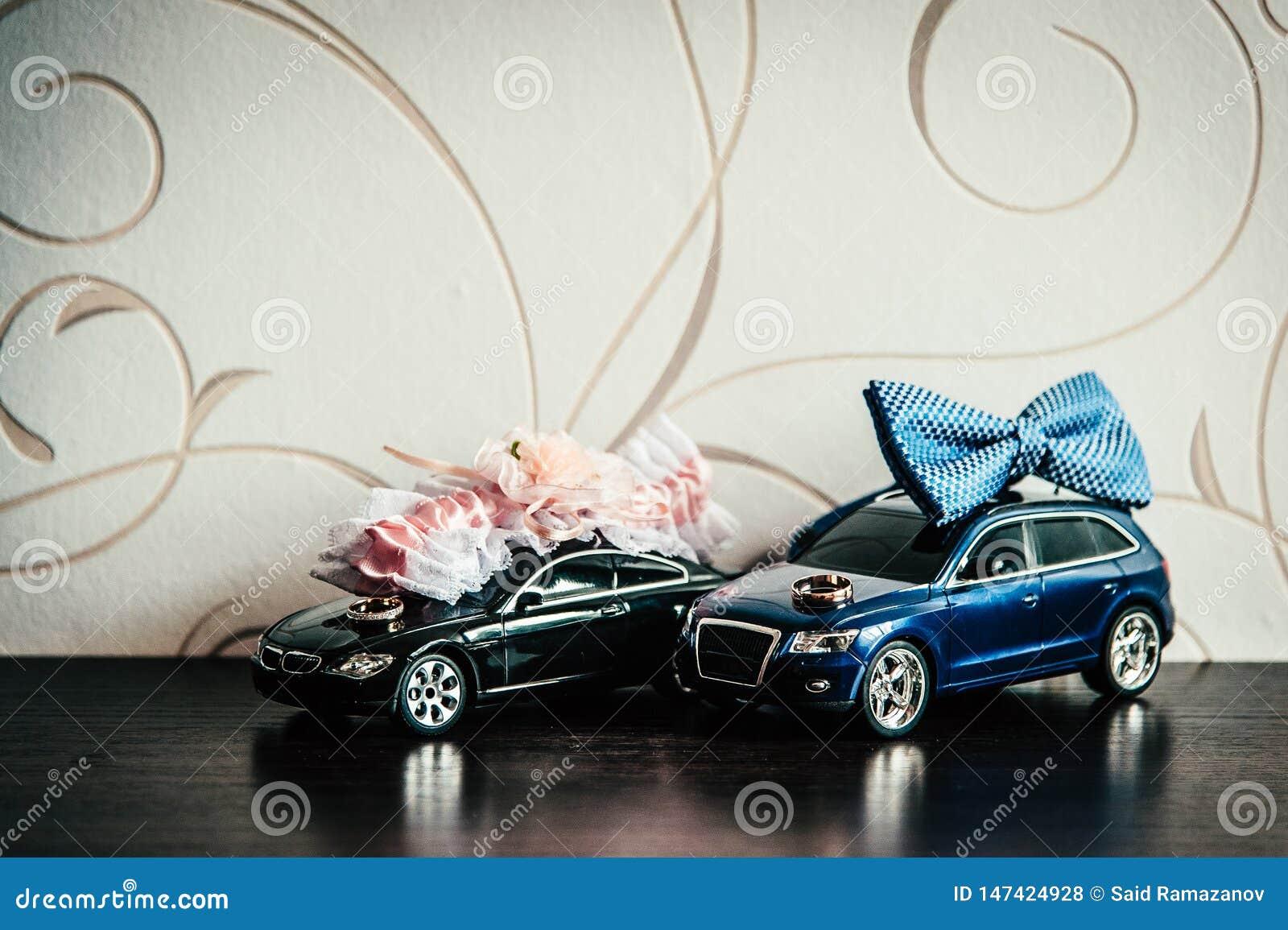Anillos de bodas, la mariposa del novio y la liga de la novia en los coches del juguete