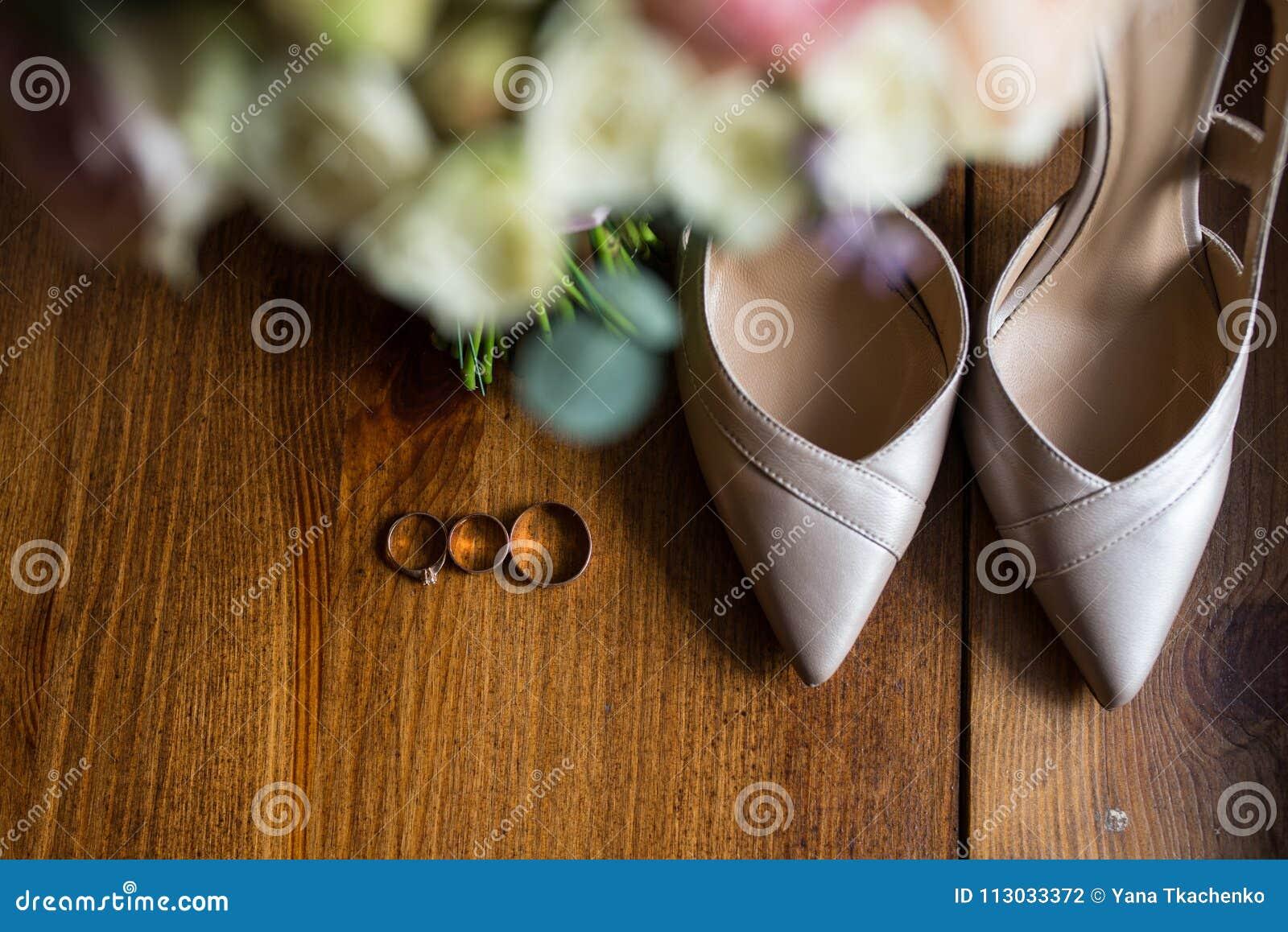Anillos de bodas de oro, anillos de compromiso y zapatos beige nupciales en fondo marrón accesorios
