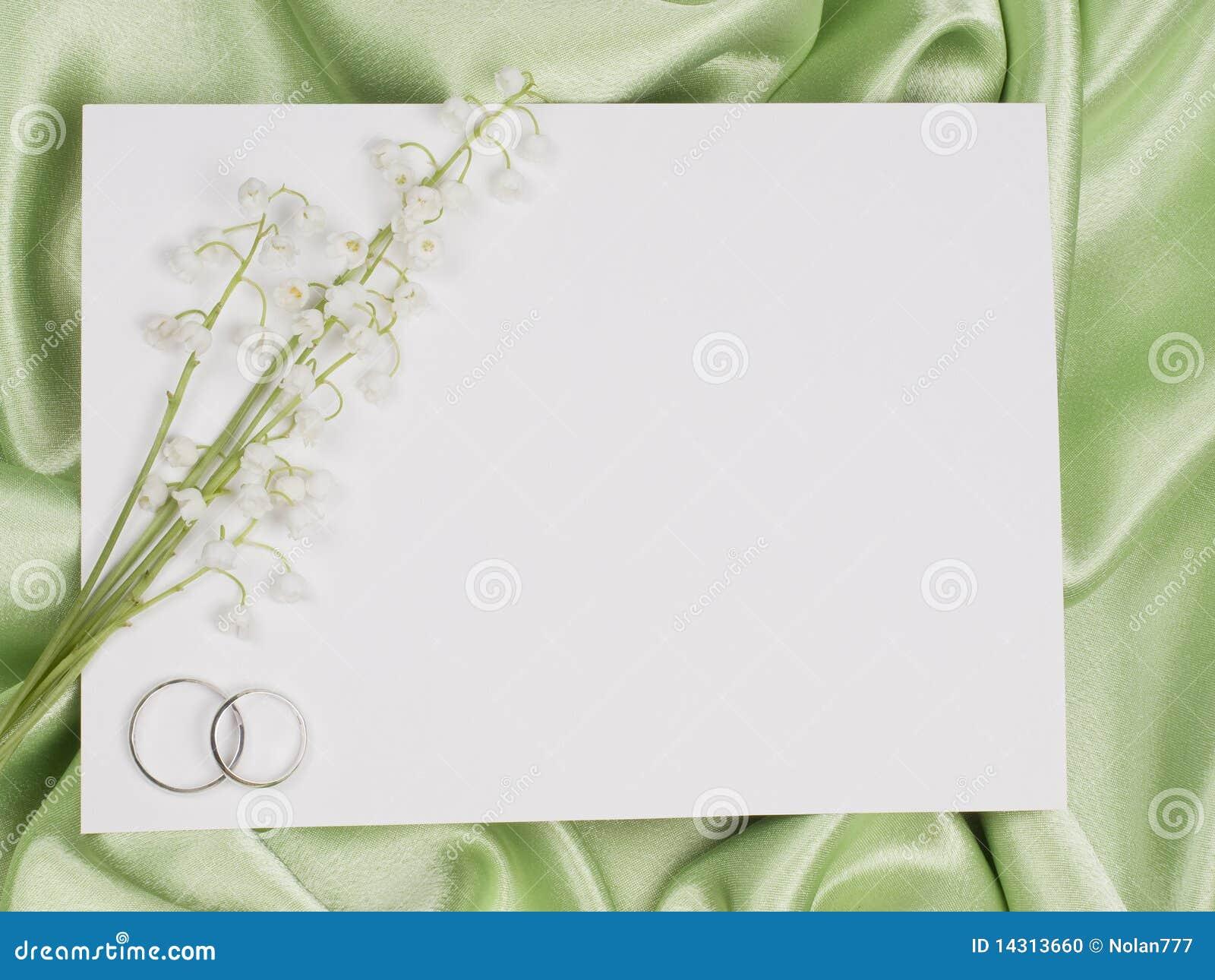 Anillos de bodas, tarjeta y lirio de los valles