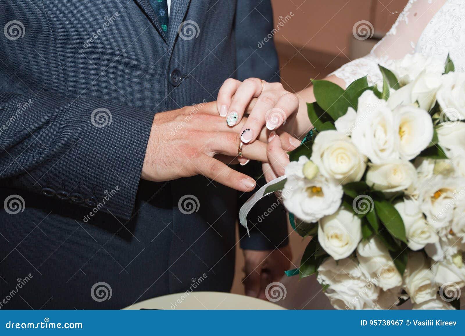 Anillos de bodas y manos de la novia y del novio pares jovenes de la boda en la ceremonia matrimonio Hombre y mujer en amor Dos