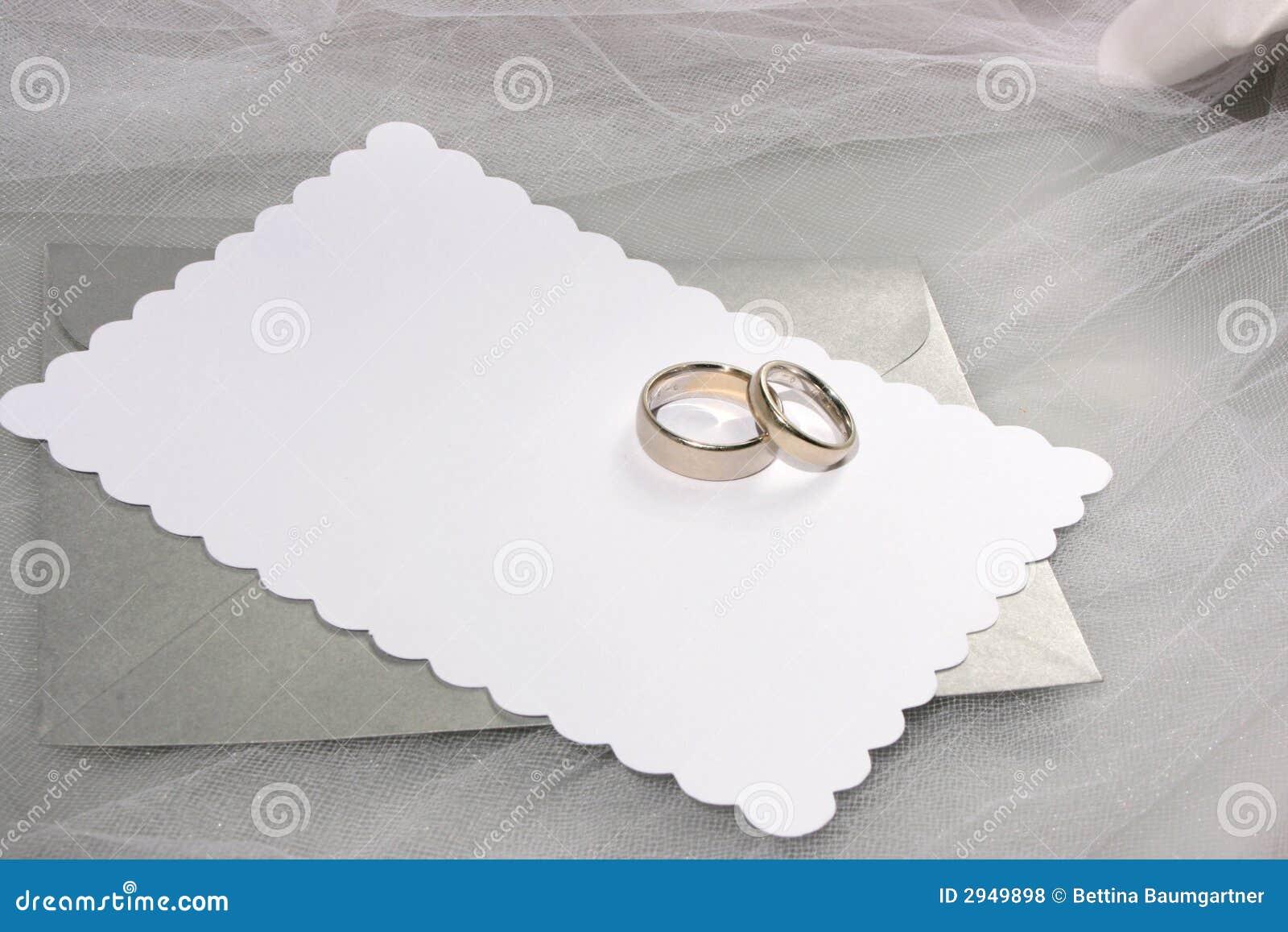 Anillos de bodas y tarjeta en blanco