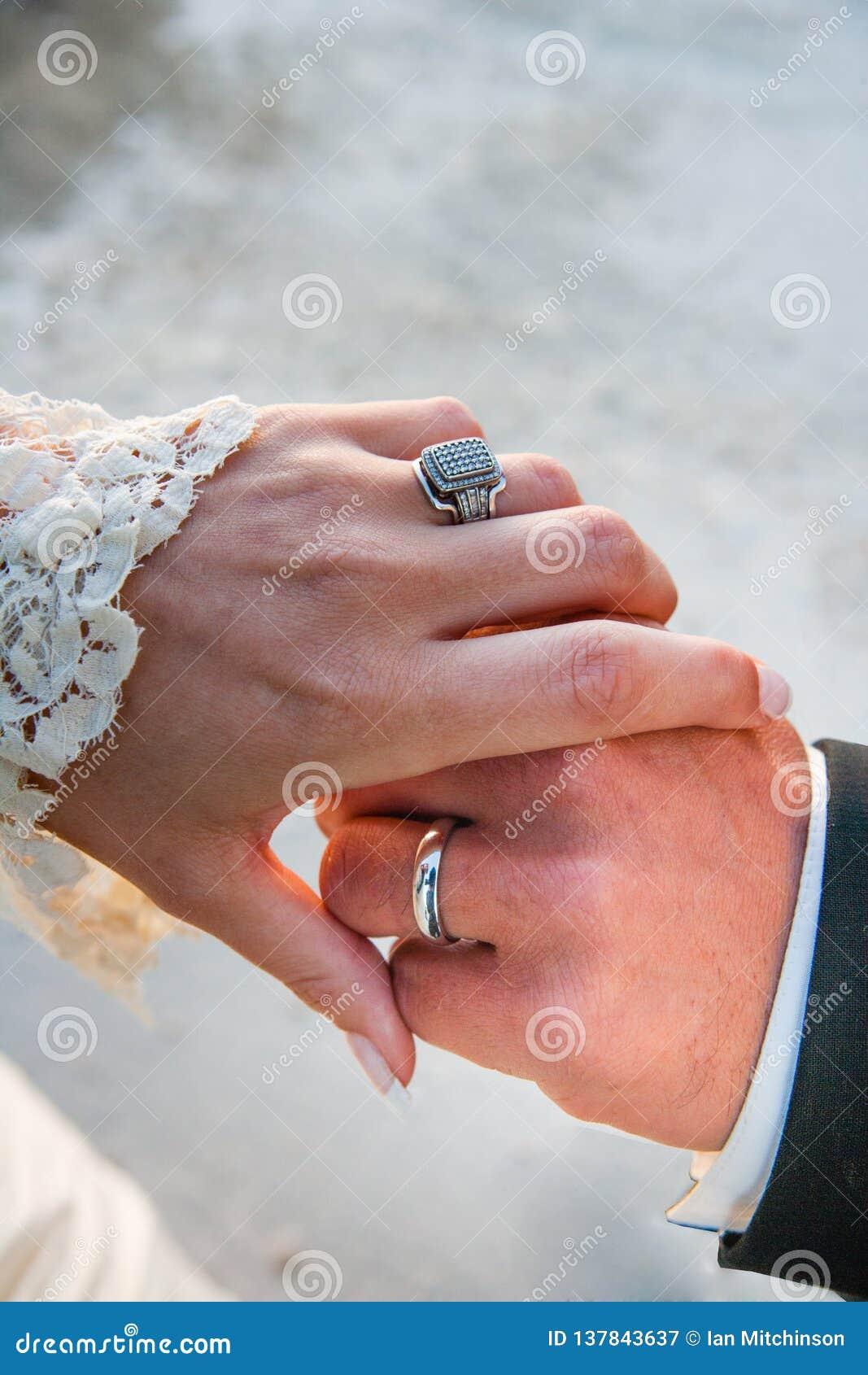 Anillos del vintage de una novia y del novio en el abarcamiento de las manos después de estar casado en una boda