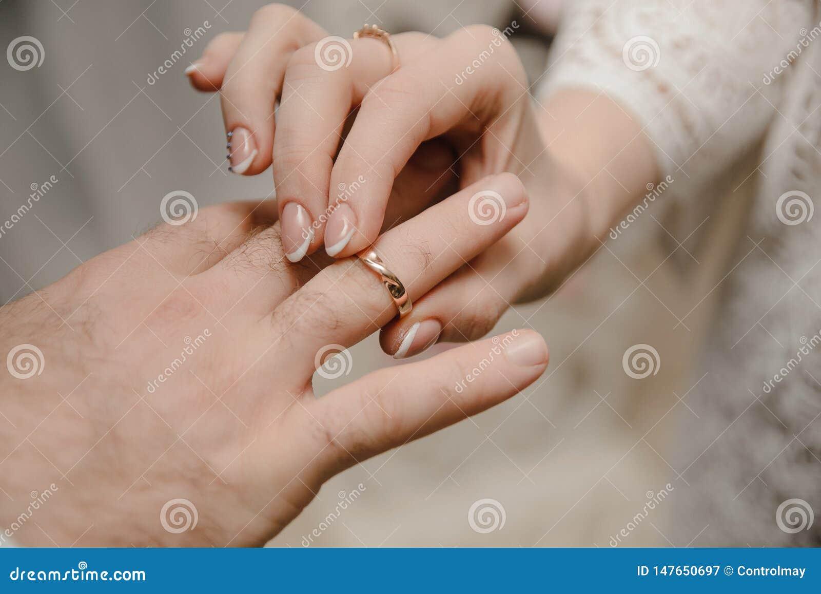 Anillos jovenes del intercambio de los pares en la ceremonia que se casa