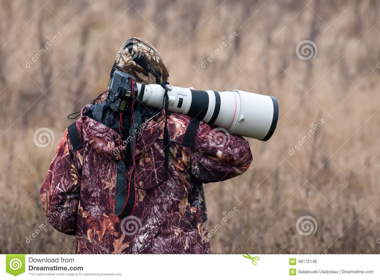 Animal Photographer. Photo Hunter. A Man In Camouflage Uniform With A Black Camera And A Large White Lens. A Man With A Camera On