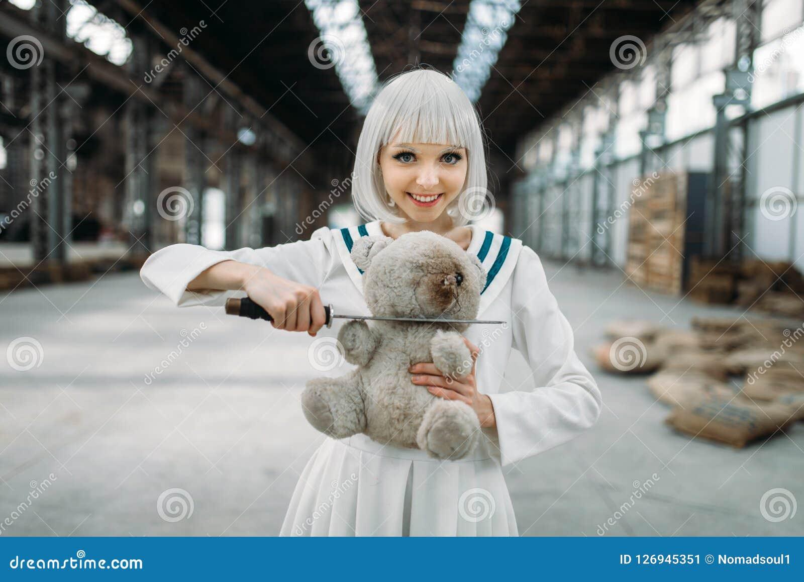 Anime style lady cuts off the head of a teddy bear