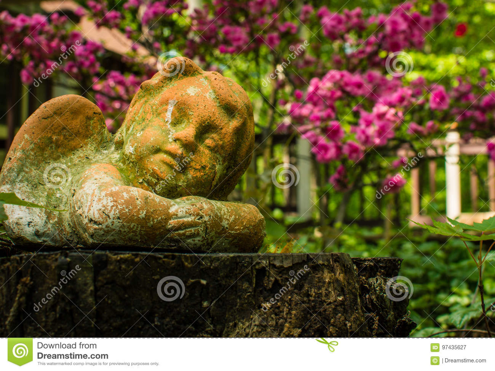 Aniołeczka ornamentu odpoczynki pokojowo wśród ogrodowych kwiatów