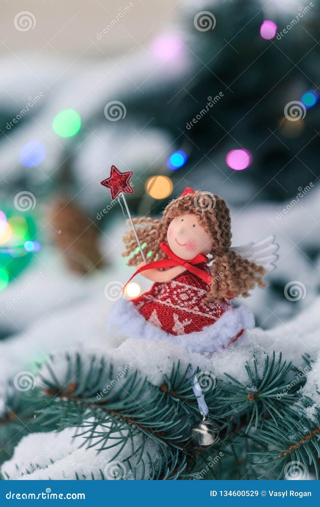 Anjo em um ramo do abeto na madeira coberto de neve Decoração do Natal