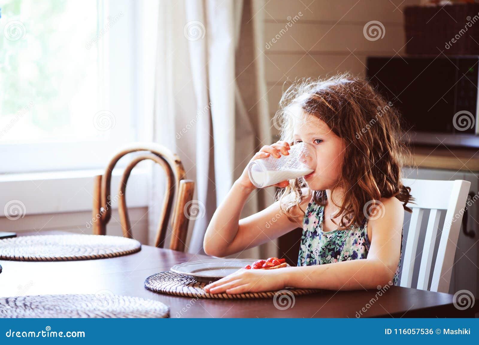 8 années heureuses de fille d enfant prenant le petit déjeuner dans la cuisine de pays