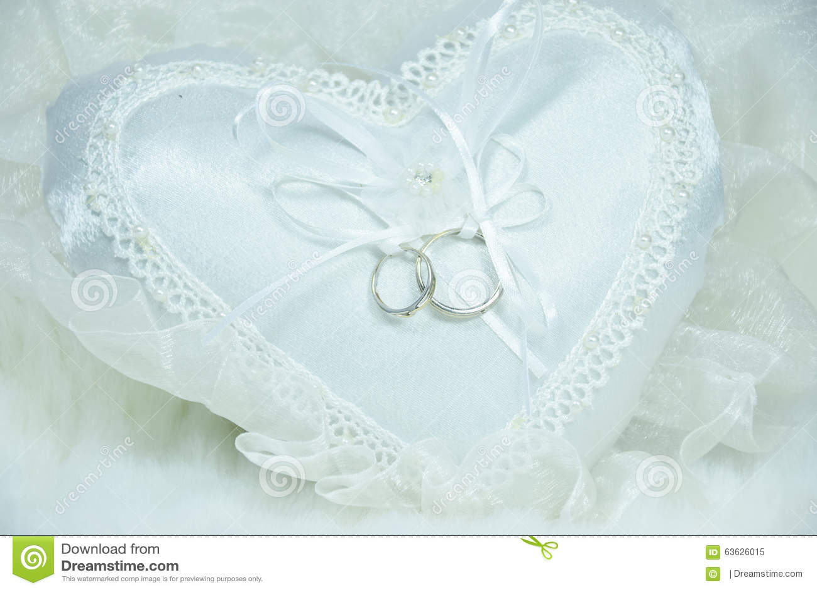 ... stock: Anneau de mariage sur l oreiller blanc et le fond mou de tissu