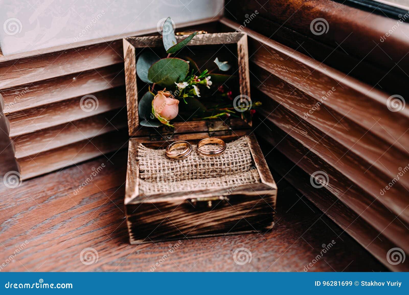 anneaux de mariage d'or dans la belle boîte rustique avec des fleurs