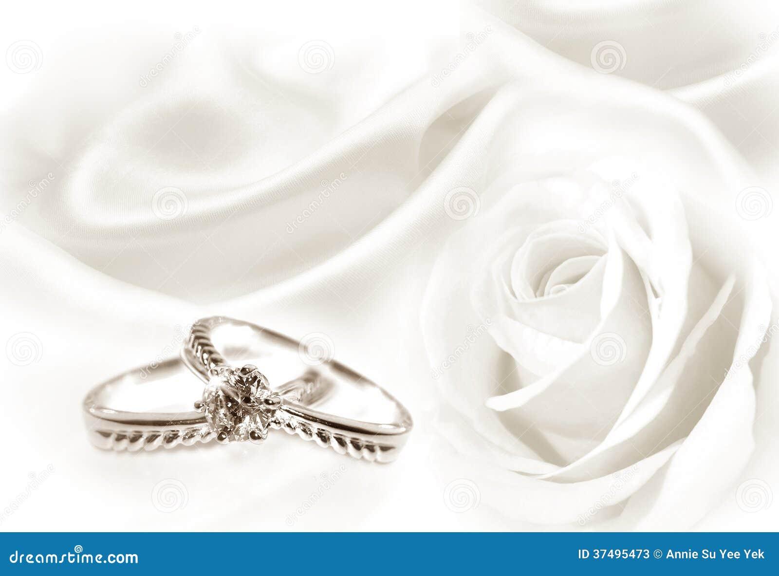 Anneaux de mariage avec un fond de rose et de tissu de blanc.