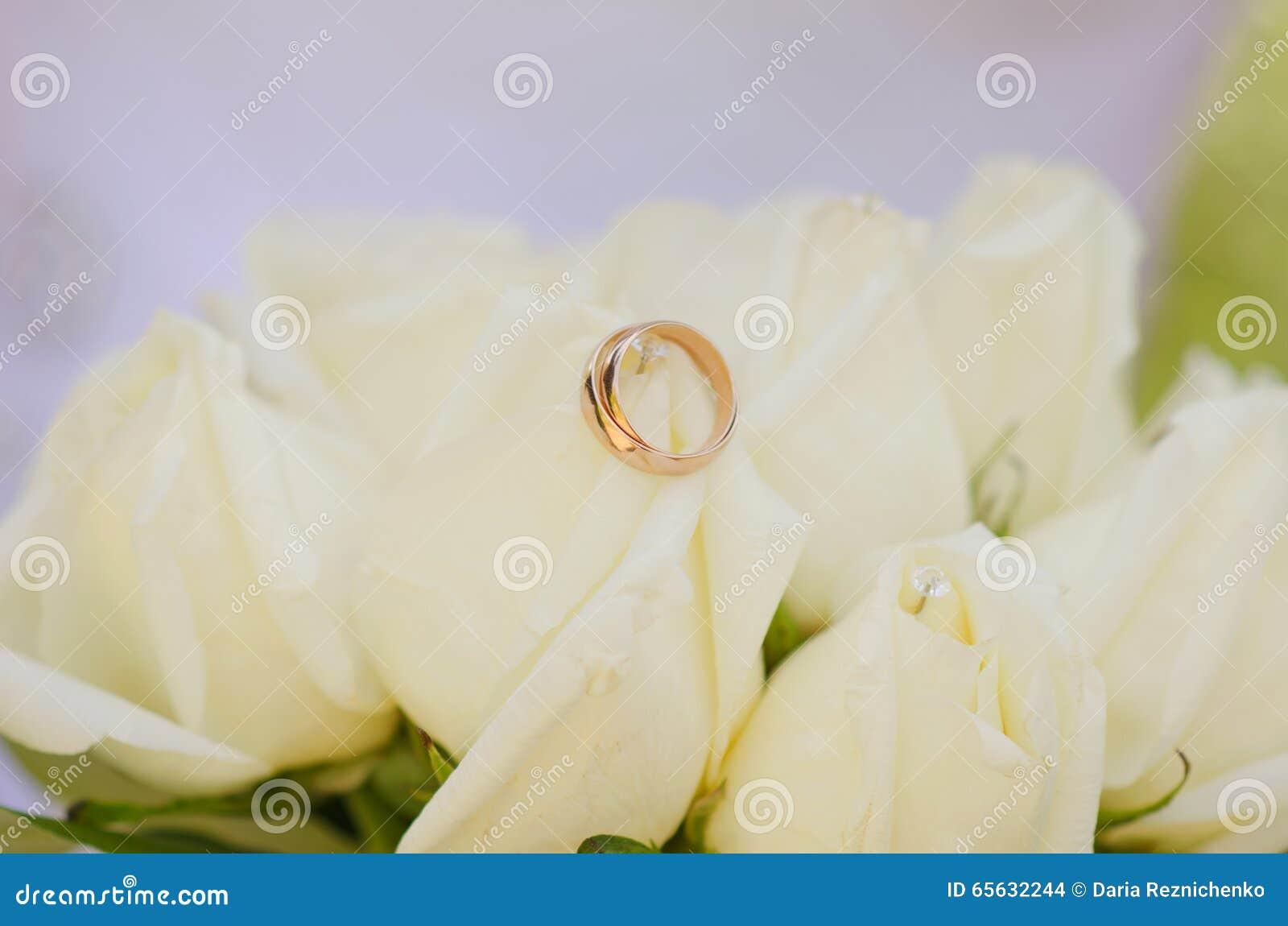 Anneaux de mariage se trouvant sur les roses blanches