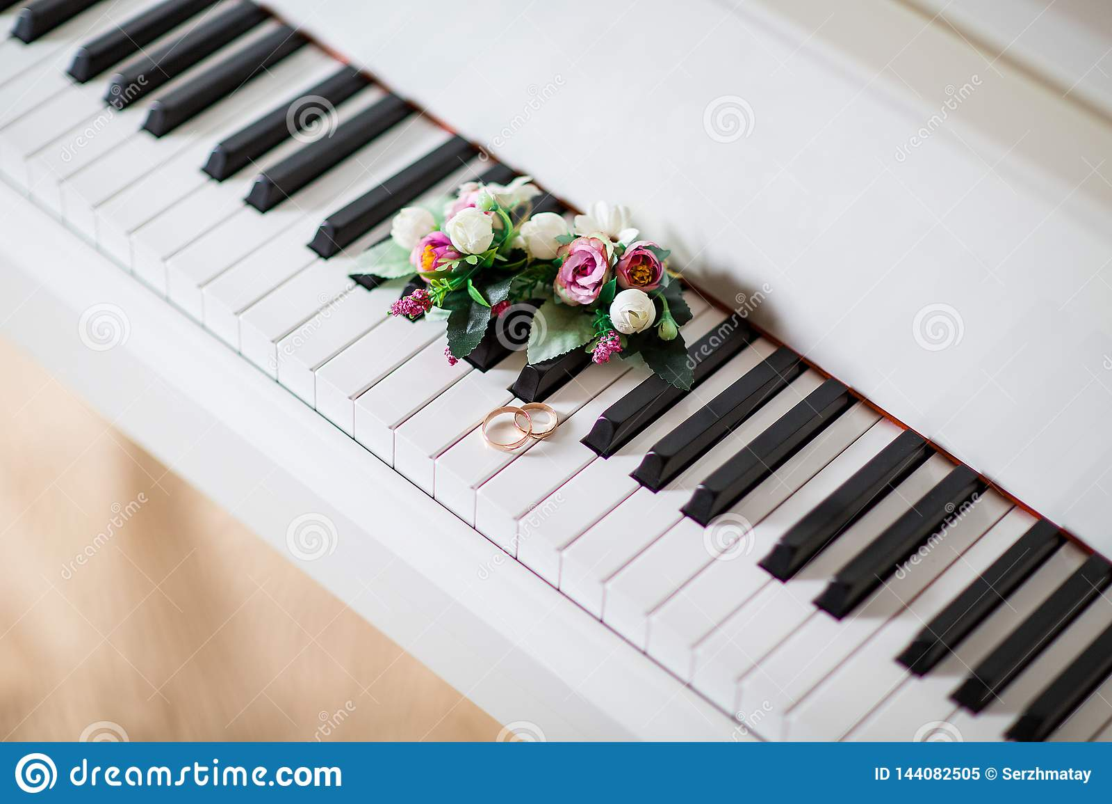 Anneaux de mariage sur le piano blanc avec des fleurs