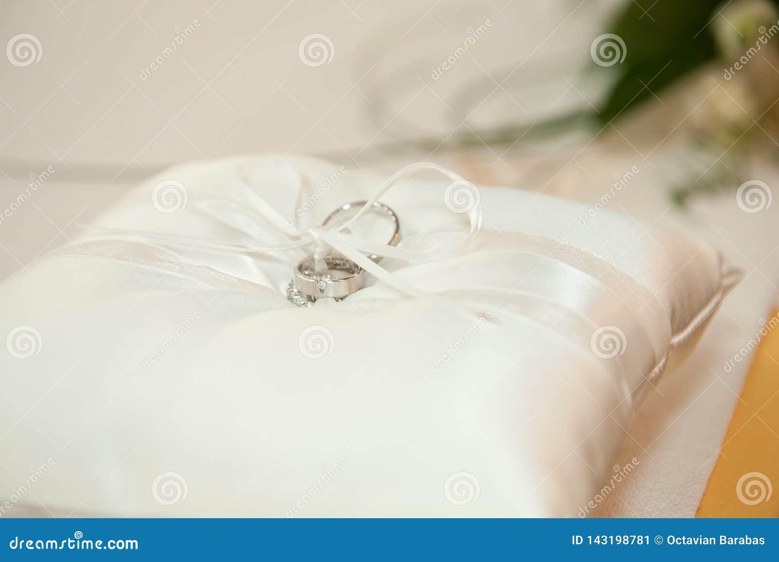 Anneaux de noces d argent sur un oreiller en soie blanc