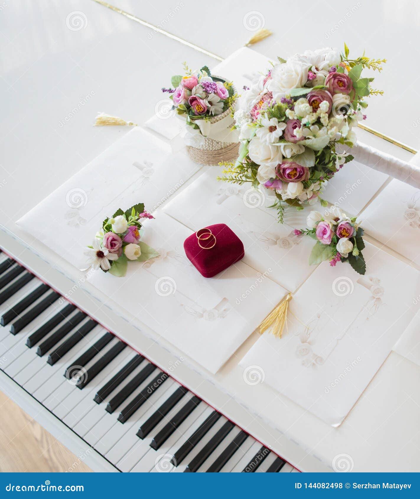 Anneaux les épousant sur un piano blanc