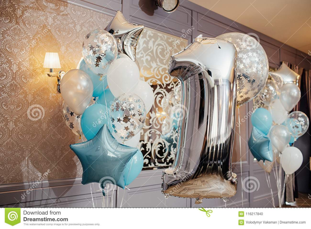 Anniversary or birthday photo zone with white, blue and transparent balloons, free space. Colorful balloons background, one year.