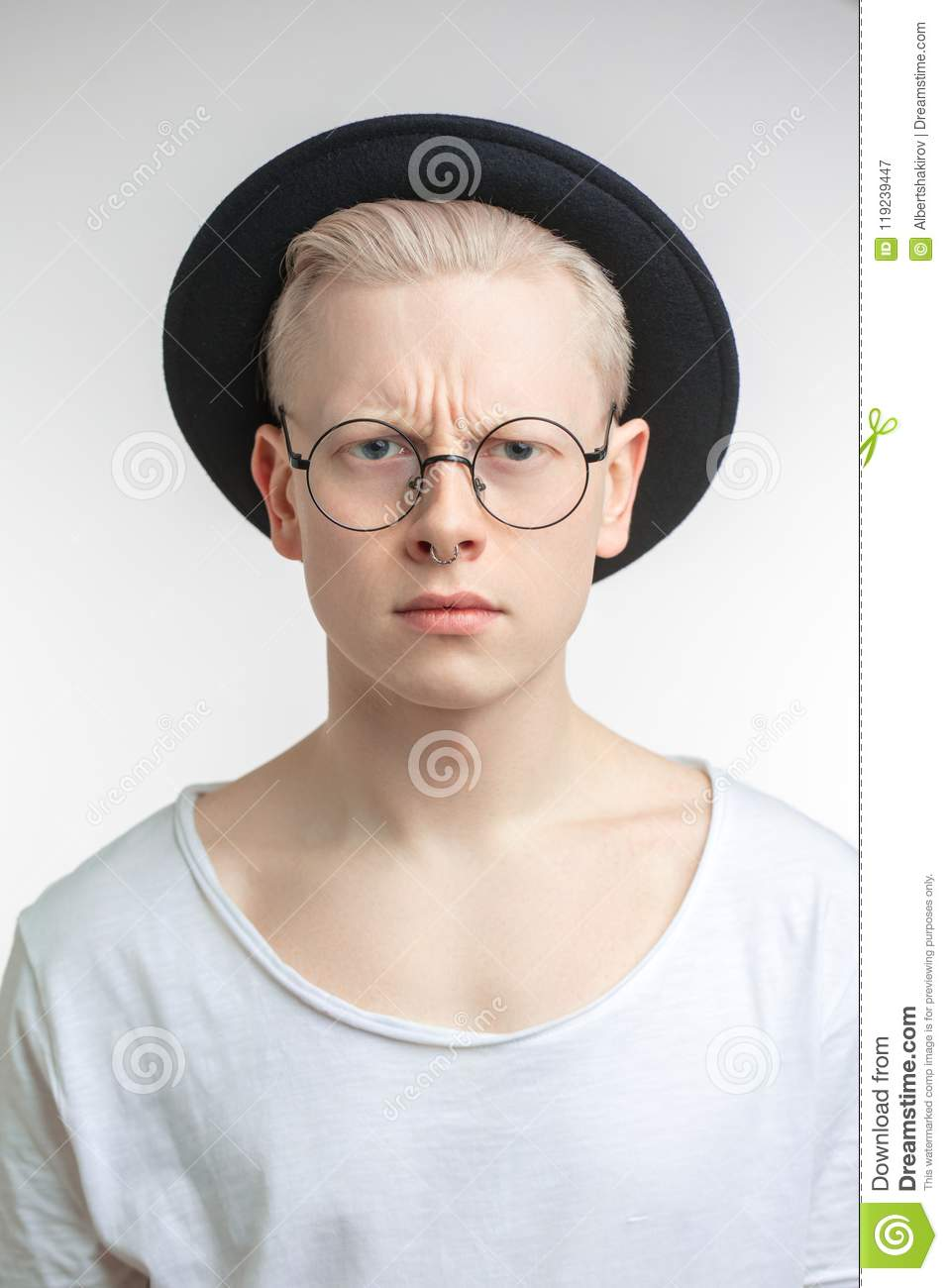 f4f062a2229 Dissatisfied handsome blonde hipster man with frowned brows wearing black  hat over white background. People negative emotions concept