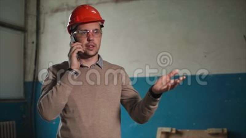 5d9e289a4bd6a Annoyed Engineer Talking On Mobile Phone At Work Stock Footage - Video of  angry