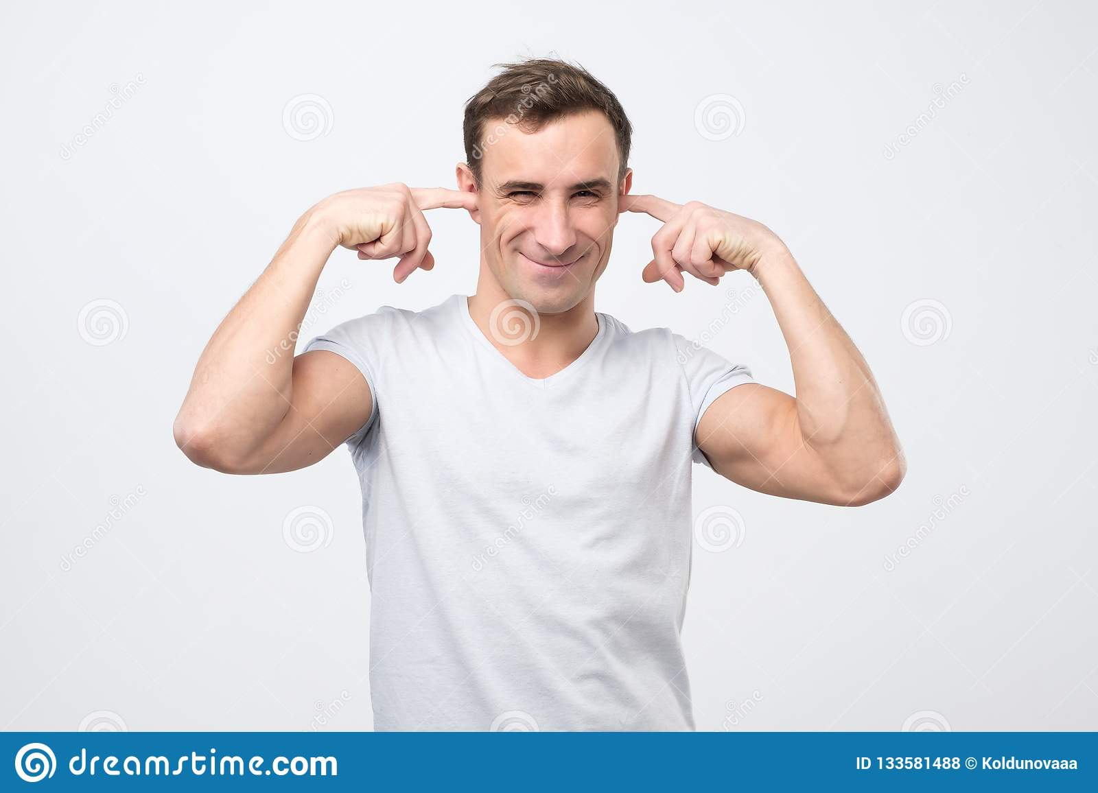 Annoyed mature italian man plugging ears with fingers