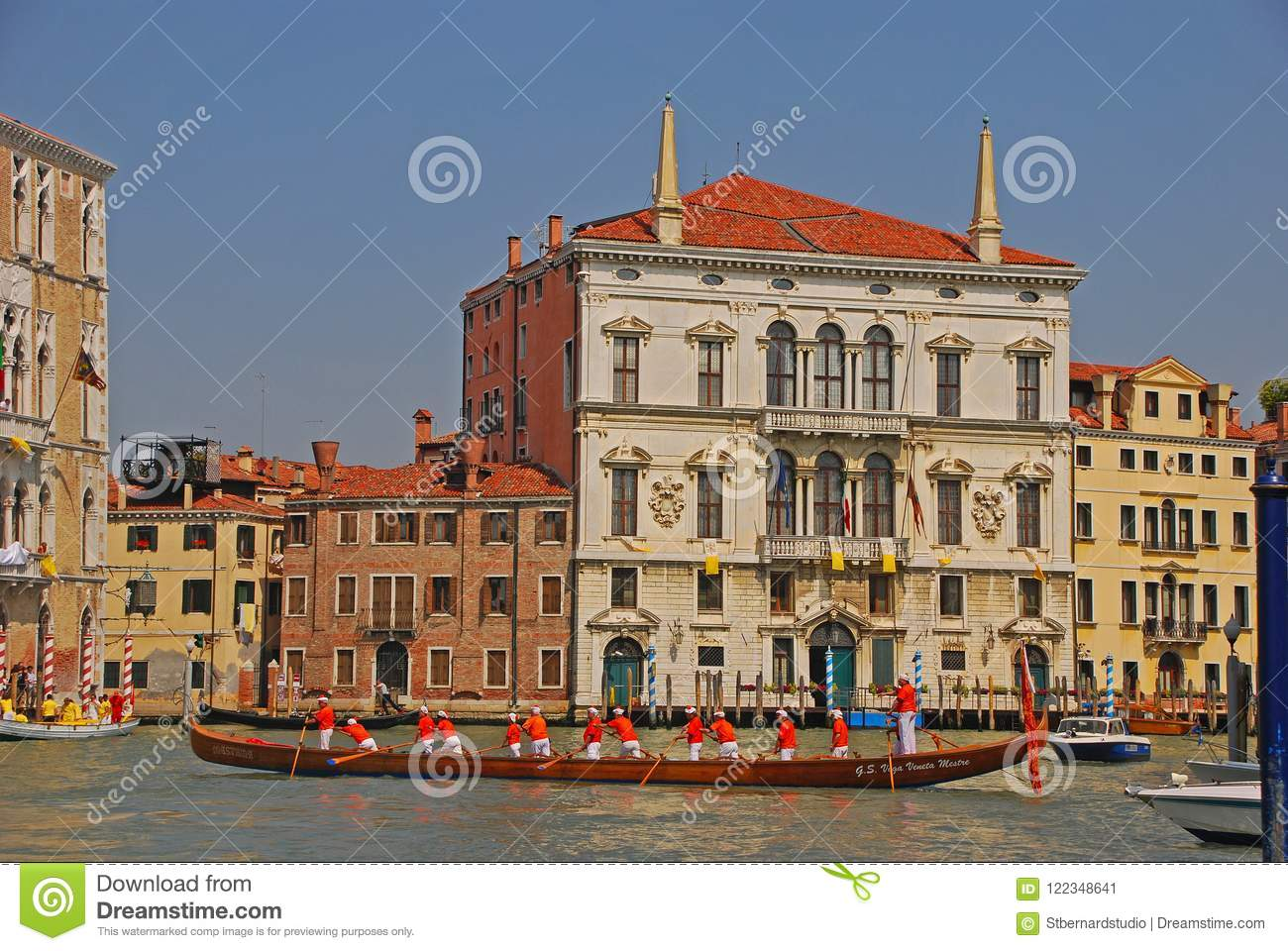 A group of elderly boat rowers with a very long boat taking a rest during the Vogalonga Regatta festival in Venice, Italy