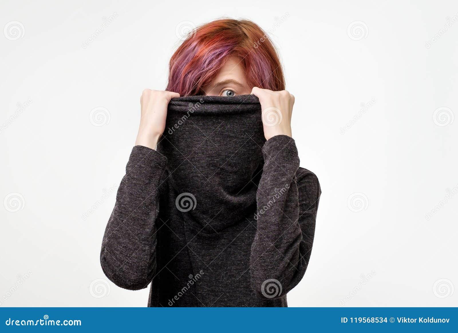 Anonimowy pojęcie Młoda kobieta z ciekawą kolorową fryzurą chuje jej twarz z kołnierzem