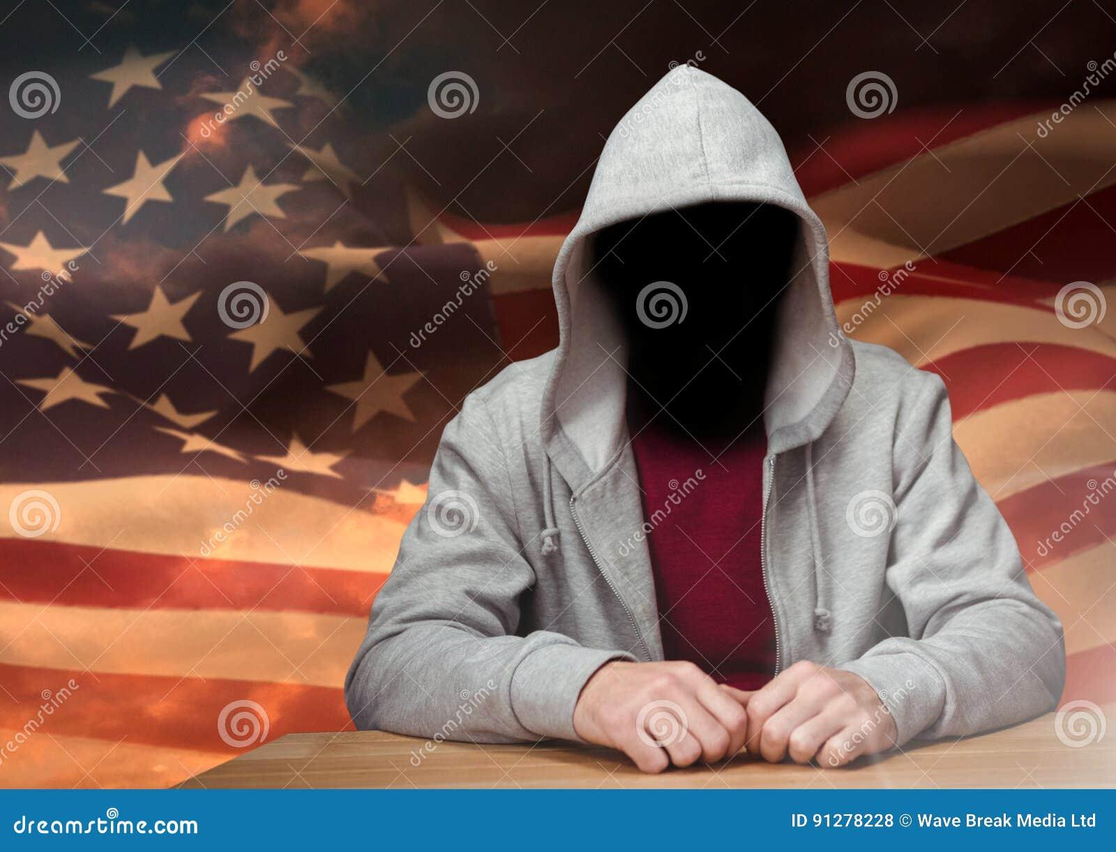 Anonym brottsling i huv framme av amerikanska flaggan