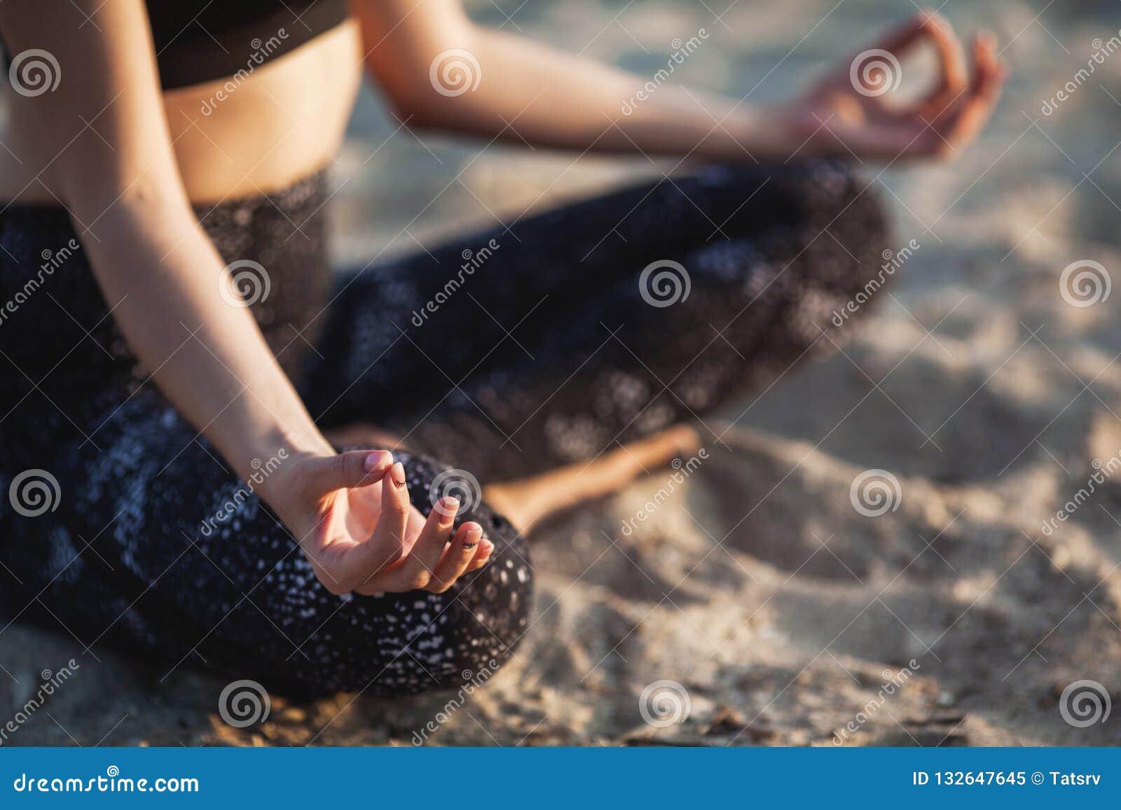 Anonym hand för närbild av kvinnan i Lotus Position At sandstrand