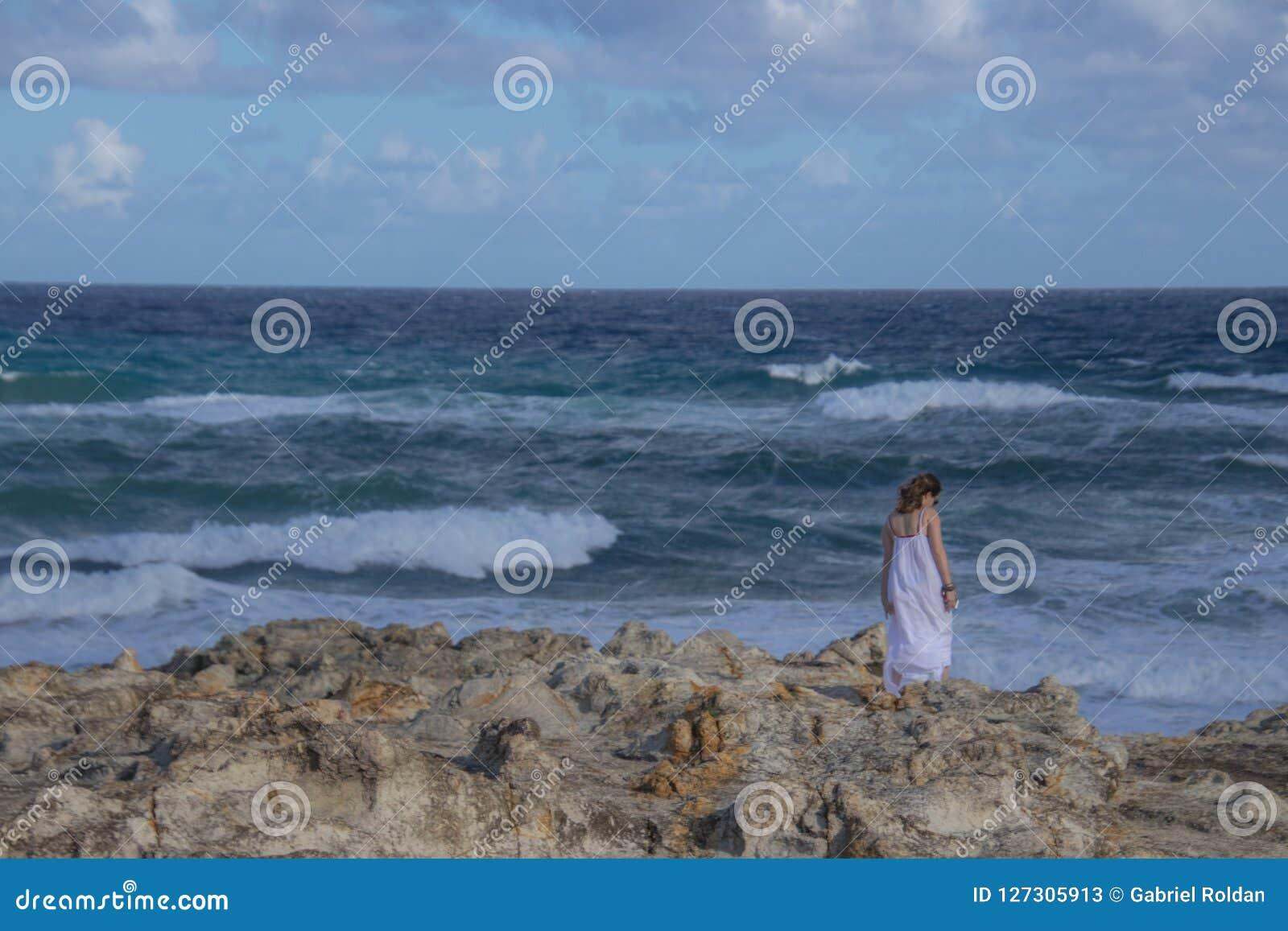 Anonym kvinna som står nära det stormiga havet