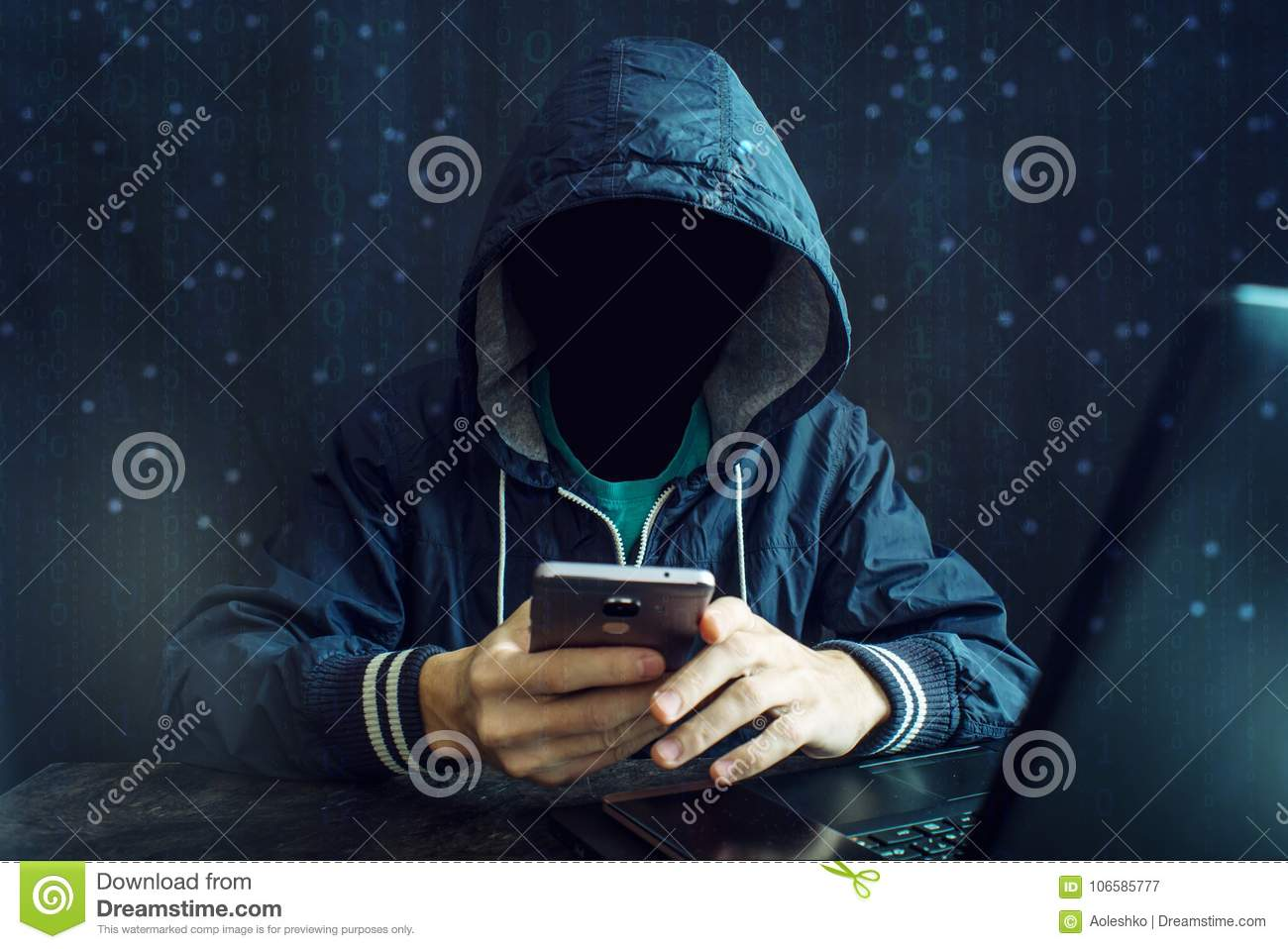 An anonymous hacker without a face uses a mobile phone to hack the system. The concept of cyber crime