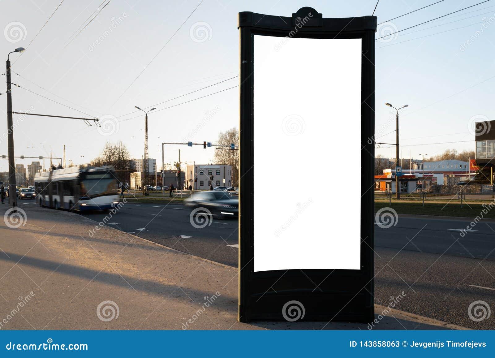 Anseende för affischtavla för gata för annonsmodellmellanrum nära en väg med att flytta suddiga bilar - lång exponering under en