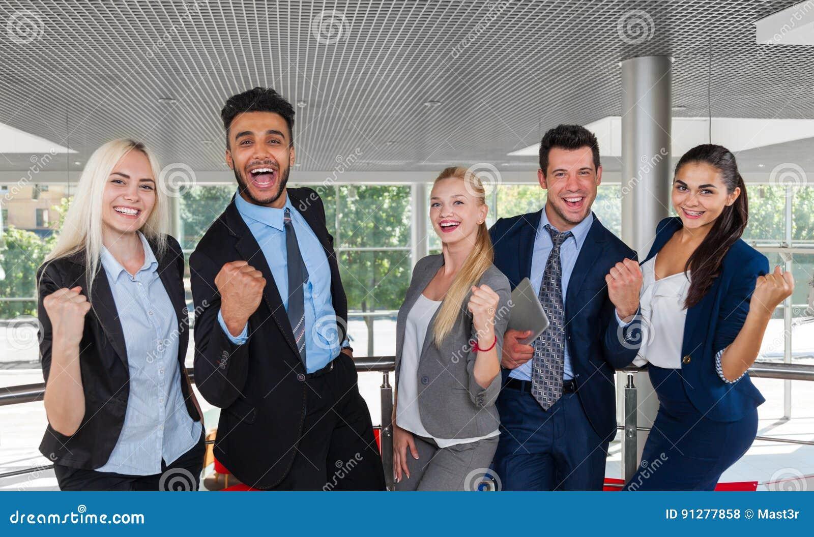Anseende för leende för grupp för affärsfolk lyckligt på modern lyftta händer för kontorsBusinesspeople framgång
