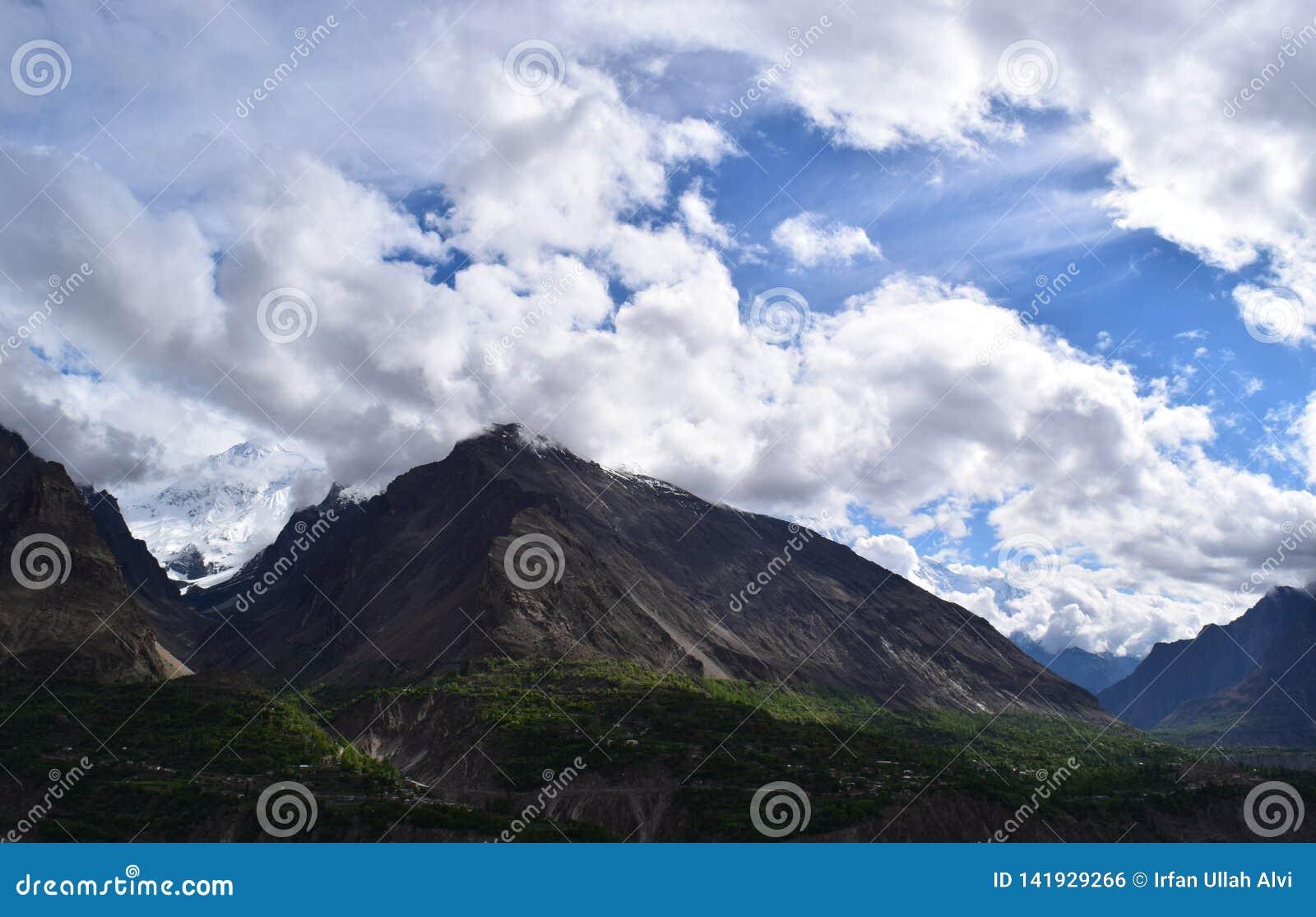 Ansicht über den Hügel mit Gebirgspfad und die schneebedeckten Berge auf dem Hintergrund