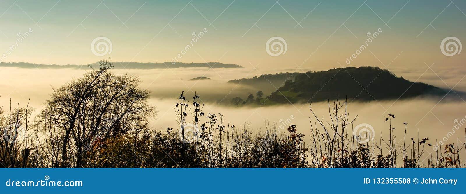 Ansicht bei Sonnenuntergang des Nockens der lang unten und Hügel von Uley-Fort nahe zu Uley, Gloucestershire