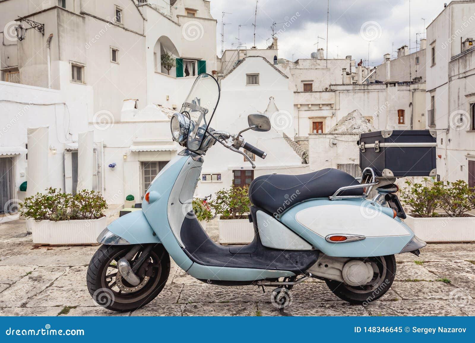 Ansicht der alten Stadt von Martina Franca Klassisches blaues Moped auf dem Hintergrund von anient Geb?ude