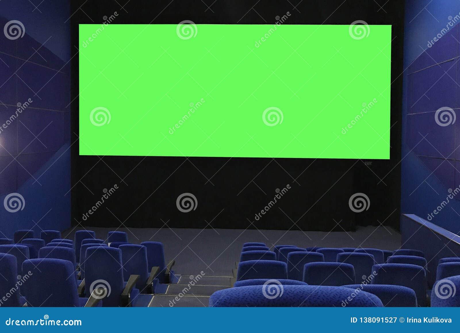 Ansicht der leeren Kinohalle und des großen grünen Schirmes von den oberen Reihen Kino mit Reihen von blauen Stühlen