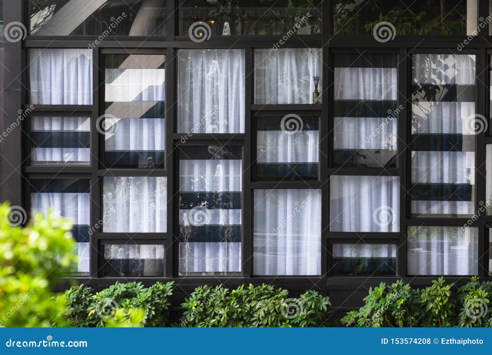 Ansicht der modernen Fenster und des weißen Vorhangs, dessen Glas den gegenüberliegenden Brunnen und den Garten reflektiert Abstr
