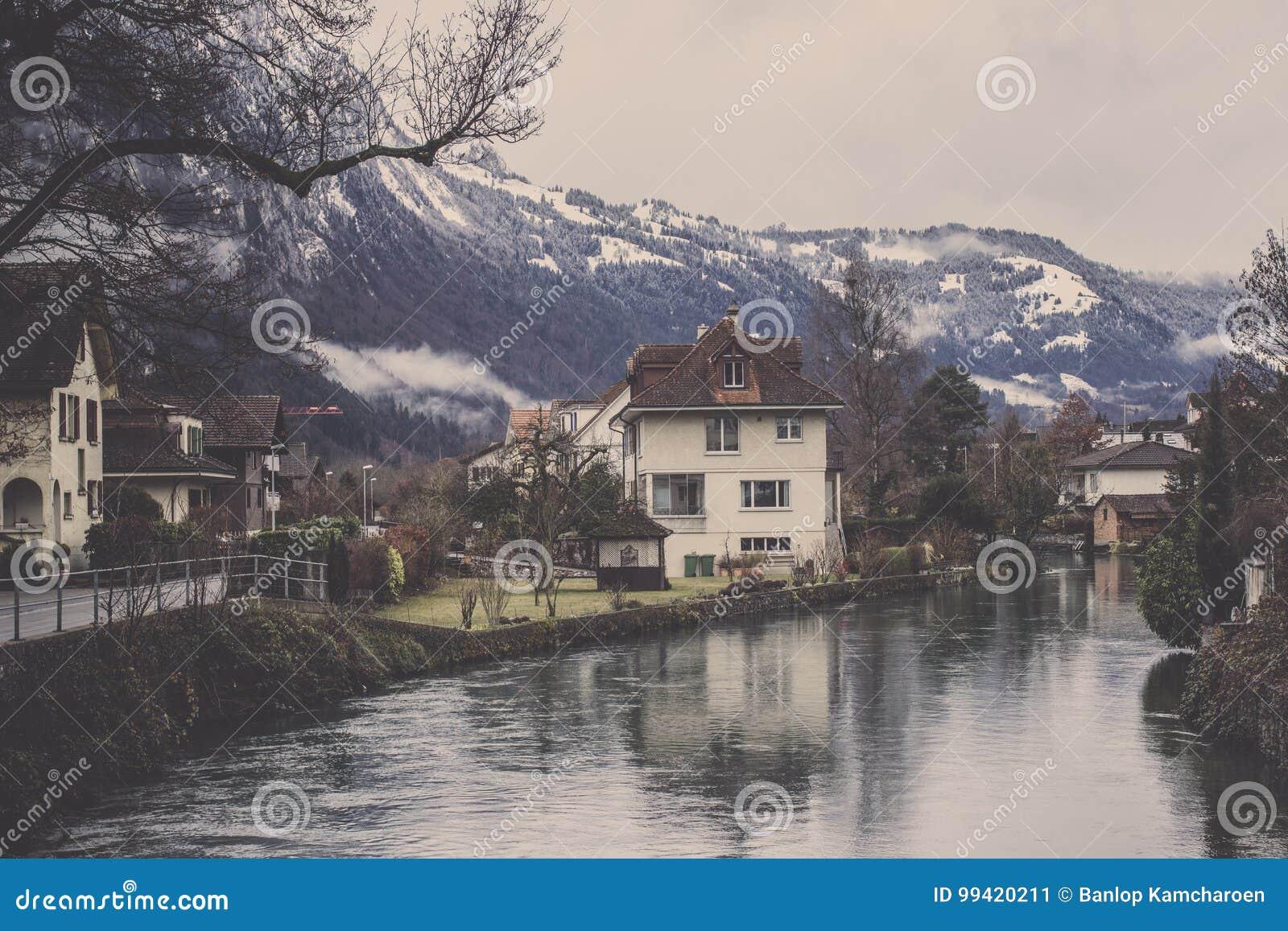 Ansicht des Dorfs mit Kanal- und Gebirgszughintergrund