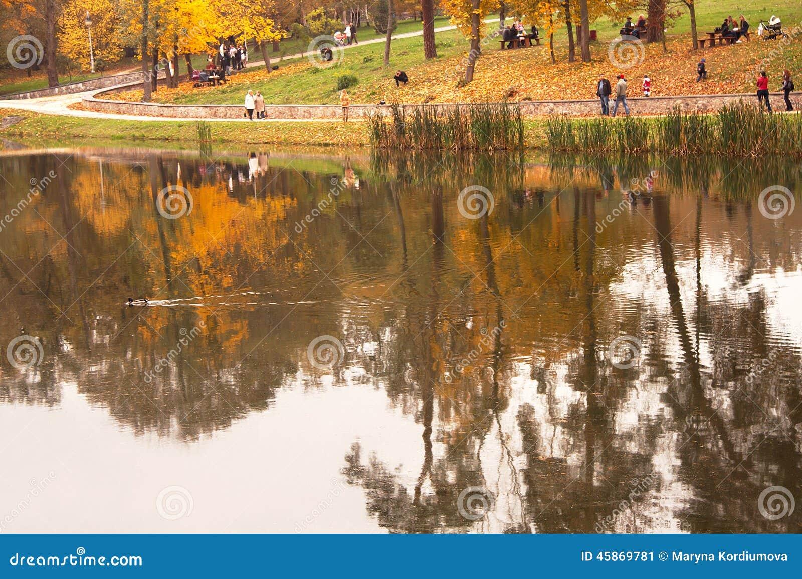 Ansicht des herbstlichen Parks mit Leute- und Baumreflexion im Wasser