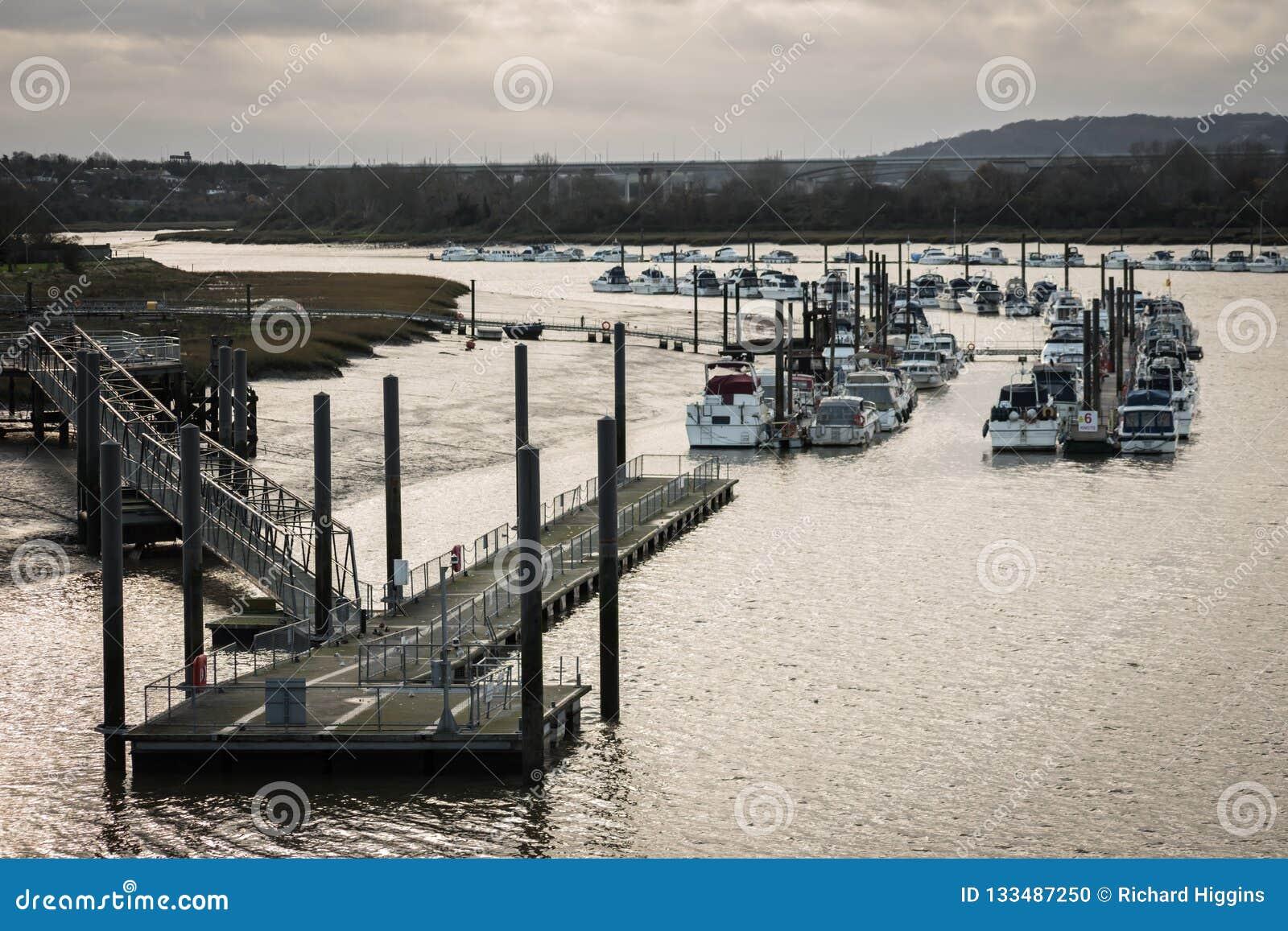 Ansicht einer Anlegestelle und des Piers, die zu eine Flotille von festgemachten Yachten auf dem Fluss Medway in Rochester, Engla