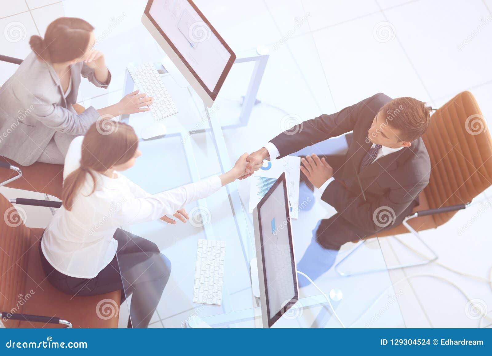 Ansicht von der Oberseite Händedruck der Senior Manager und der Angestellte über dem Schreibtisch